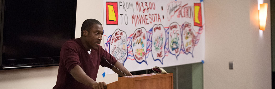 """Person at a lectern with a """"From Mizzou to Minnesota"""" banner in the background"""